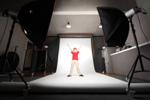 interior of professional photo studio boy in red shirt standing